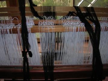 Thrading fine black wool warp on loom