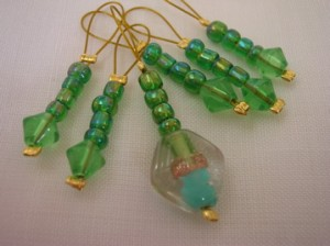 Green glass bead stitch markers with feature bead